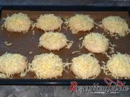 Flachgedrückte Teigkugeln mit geriebenem Käse bestreuen